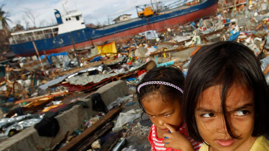 Girls look on at a destroyed community where ships washed ashore after the Super typhoon Haiyan battered Tacloban city in central Philippines Nov. 16, 2013.  (Reuters)