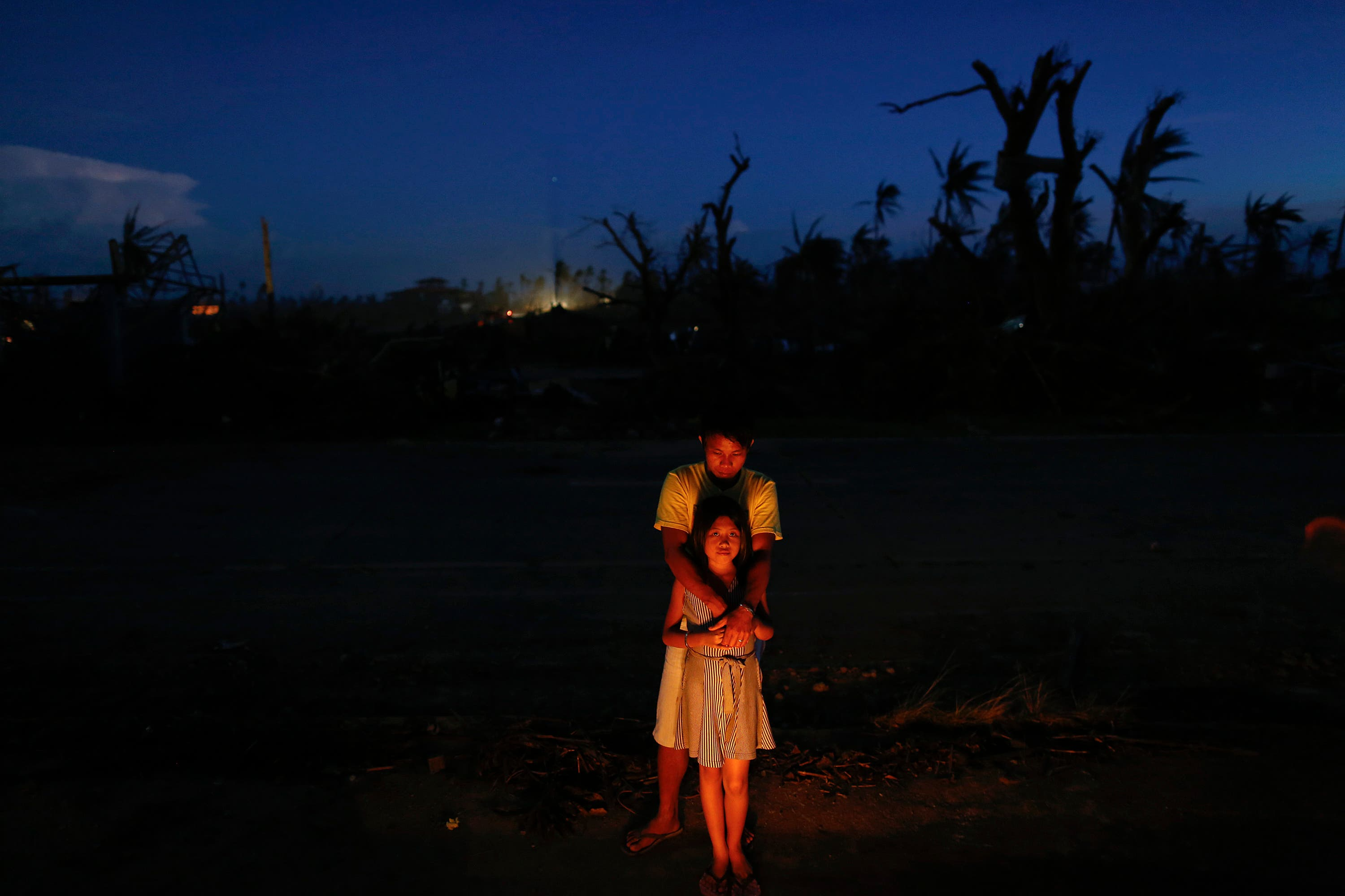 Relatives stand by candles lit on a mass grave, where they buried 17 members of their Songalia family who died when Super Typhoon Haiyan hit Leyte, by the side of a road south of Tacloban Nov. 15, 2013.  (Reuters)