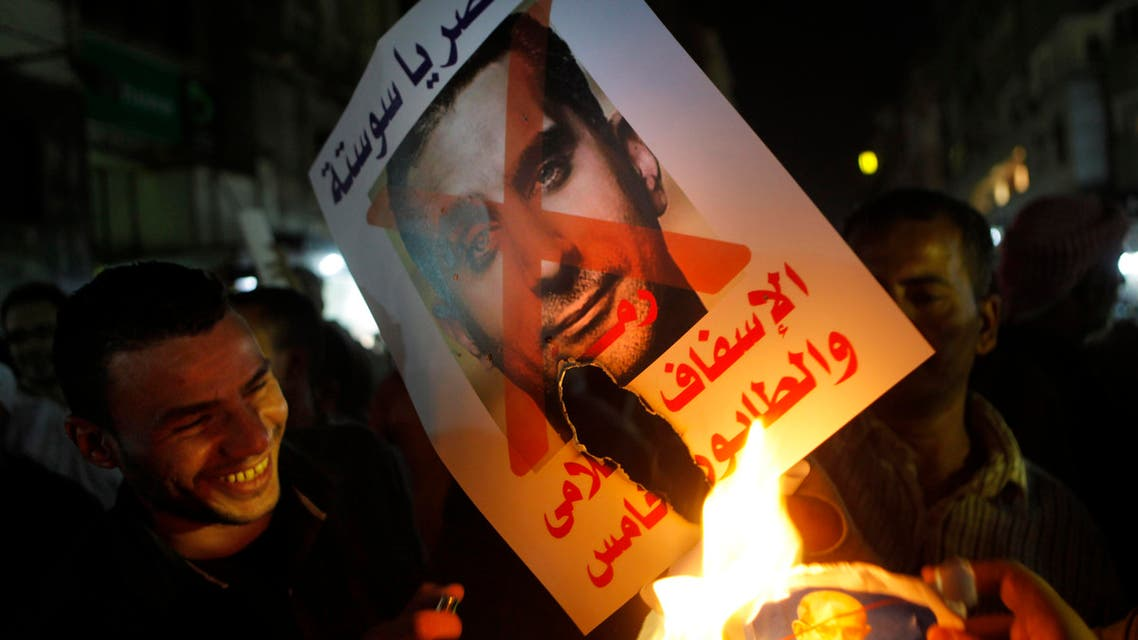 In this Wednesday, Oct. 30, 2013 photo, Supporters of army chief Gen. Abdel-Fattah al-Sisi burn a poster with a photo of Bassem Youssef. (AP)