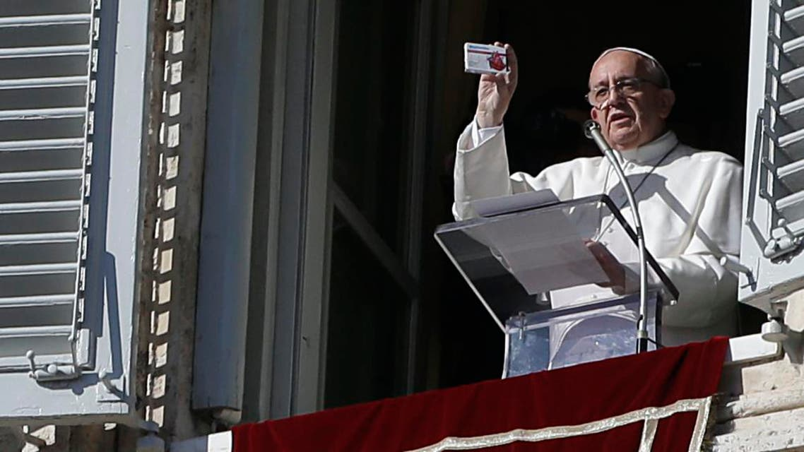 Pope Francis shows a box shaped like a pill box but which contains a rosary during his traditional Sunday appearance in St. Peter's Square at the Vatican, Sunday, Nov. 17, 2013.