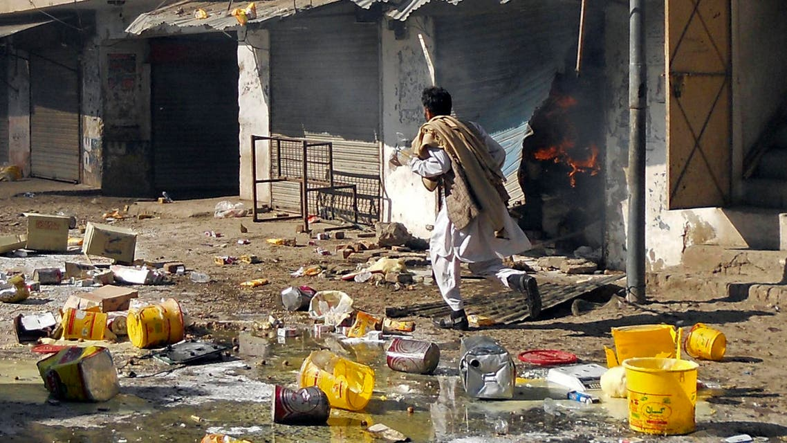 A man runs past burning shops after a market was set on fire during sectarian clashes in Kohat, Khyber Pakhtunkhwa province November 18, 2013. (Reuters)