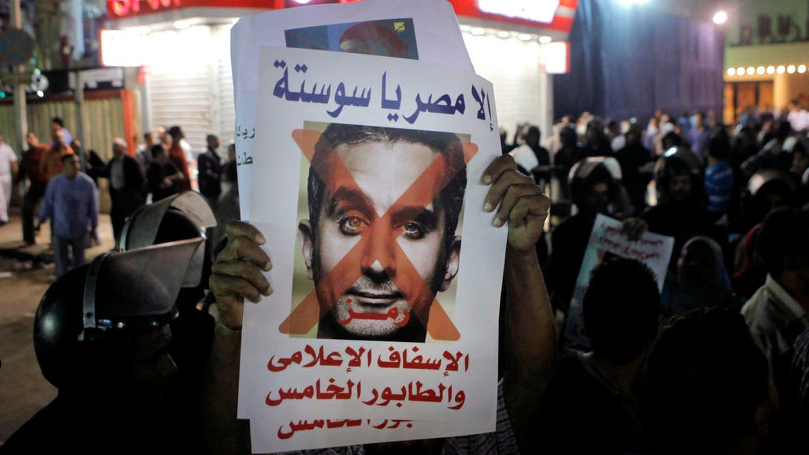 """In this Wednesday, Oct. 30, 2013 photo, A supporter of Defense Minister Gen. Abdel-Fattah el-Sisi holds a poster with a photo of Bassem Youssef, and Arabic that reads, """"not Egypt, you are degrading to the media, fifth column"""" (AP)"""