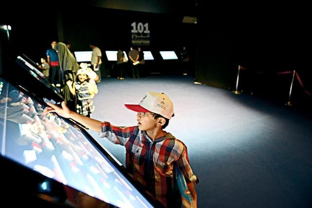 أحد الأطفال في معرض 101 اختراع غيرت العالم، يبحث عن معلومة عن أحد المخترعين في برنامج إثراء المعرفة