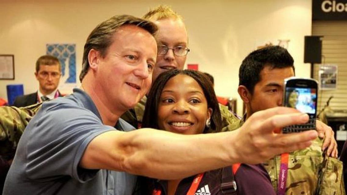 British Prime Minister David Cameron takes a selfie with Olympic volunteer Anita Akuwudike in London in August 2012. (File photo: AFP)