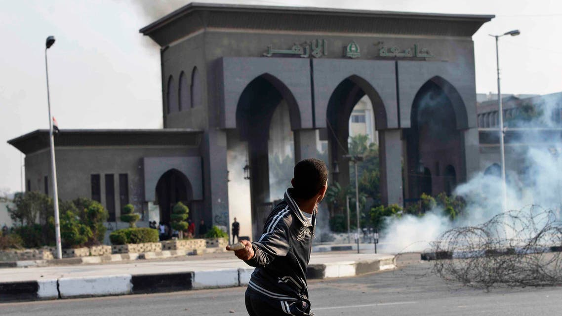 A man throws a stone in front of Al-Azhar University student members of the Muslim Brotherhood and supporters of ousted Egyptian President Mohamed Mursi, as riot police fired tear gas to stop them marching towards Rabaa al-Adaweya square, in Cairo October 28, 2013. reuters