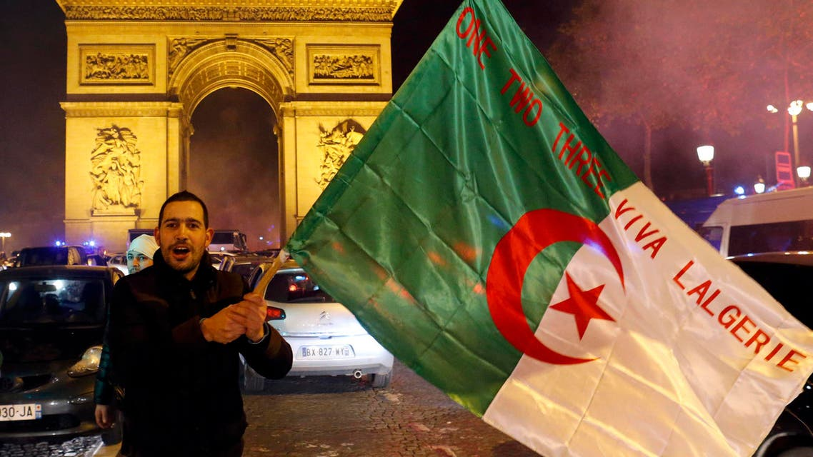 An Algeria soccer team fan celebrates with their national flag on the Champs Elysees in Paris after their team defeated Burkina Faso in their 2014 World Cup qualifying second leg playoff soccer match, Nov. 19, 2013. (Reuters)