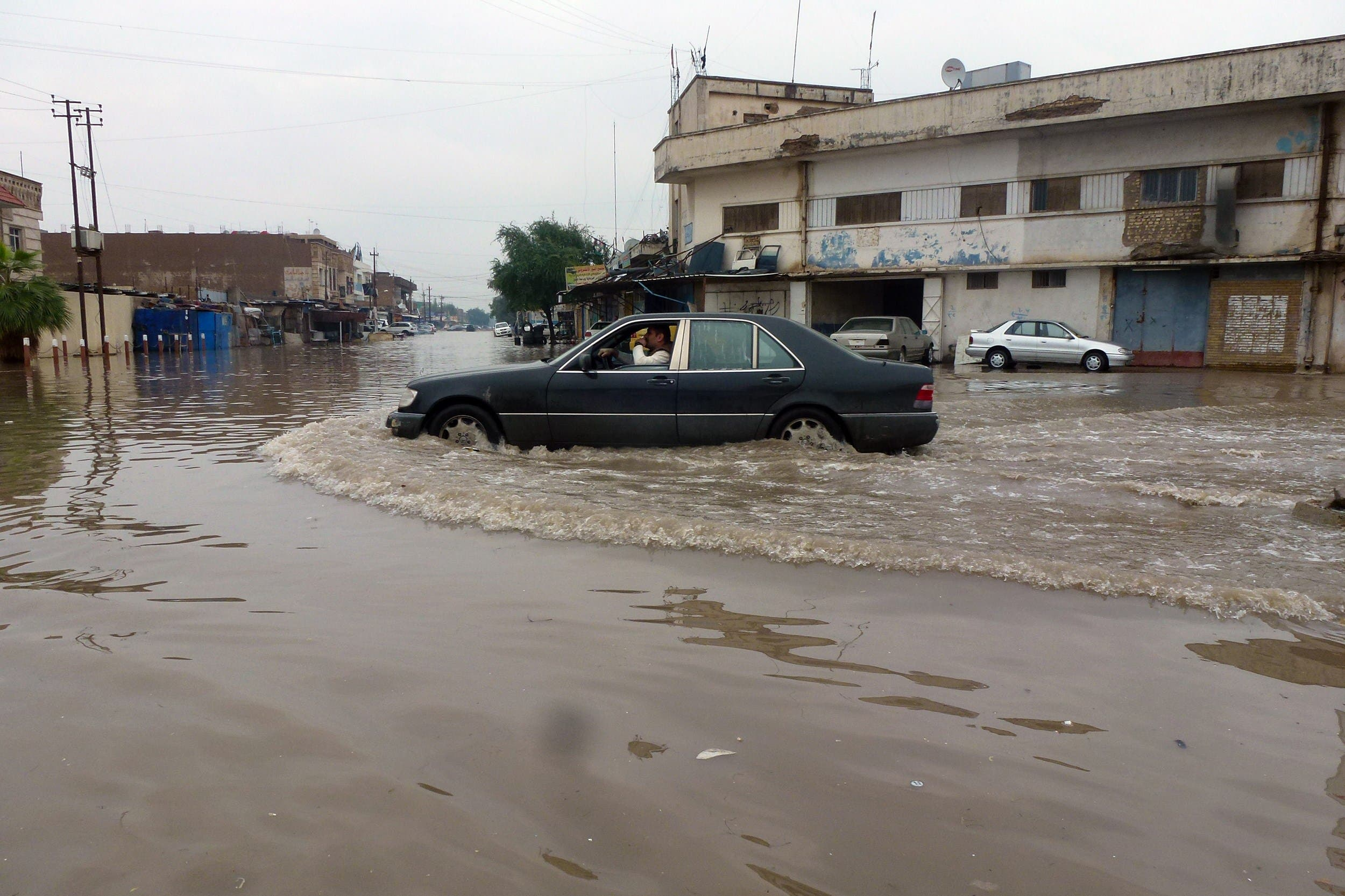 An Iraqi man drives his car through a flooded street in Baghdad on November 20, 2013, as flash floods sparked by torrential rain swept throught region. (AFP)