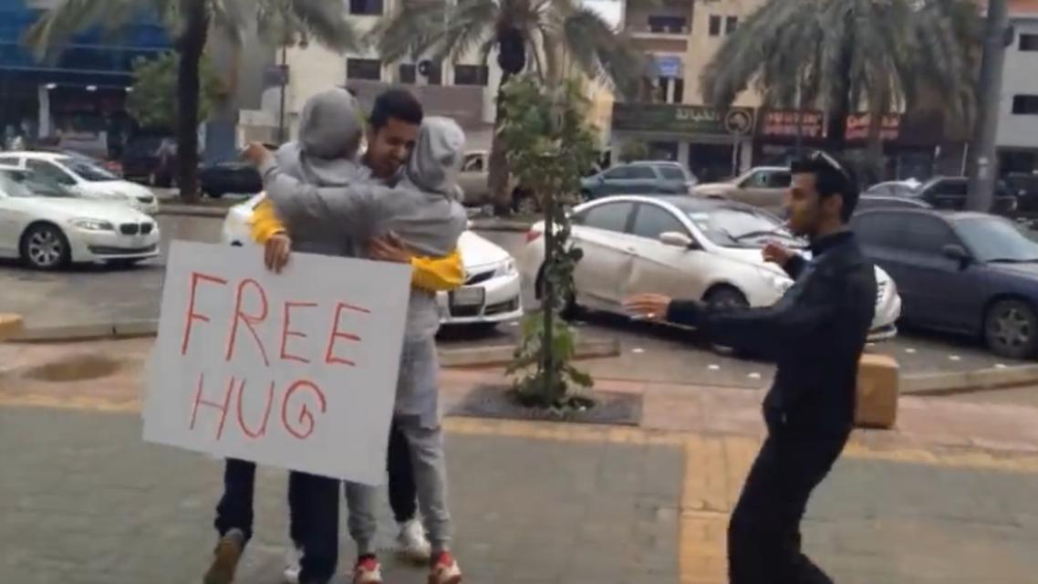 """شاب سعودي يحمل لافته """"free hug"""" في أحد شوارع الرياض"""