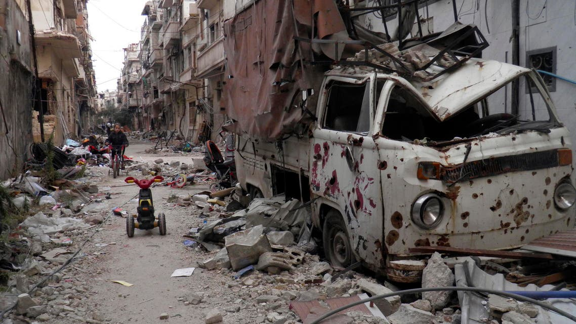 A girl rides a bicycle amidst damaged buildings and vehicles along a street in the besieged area of Homs reuters
