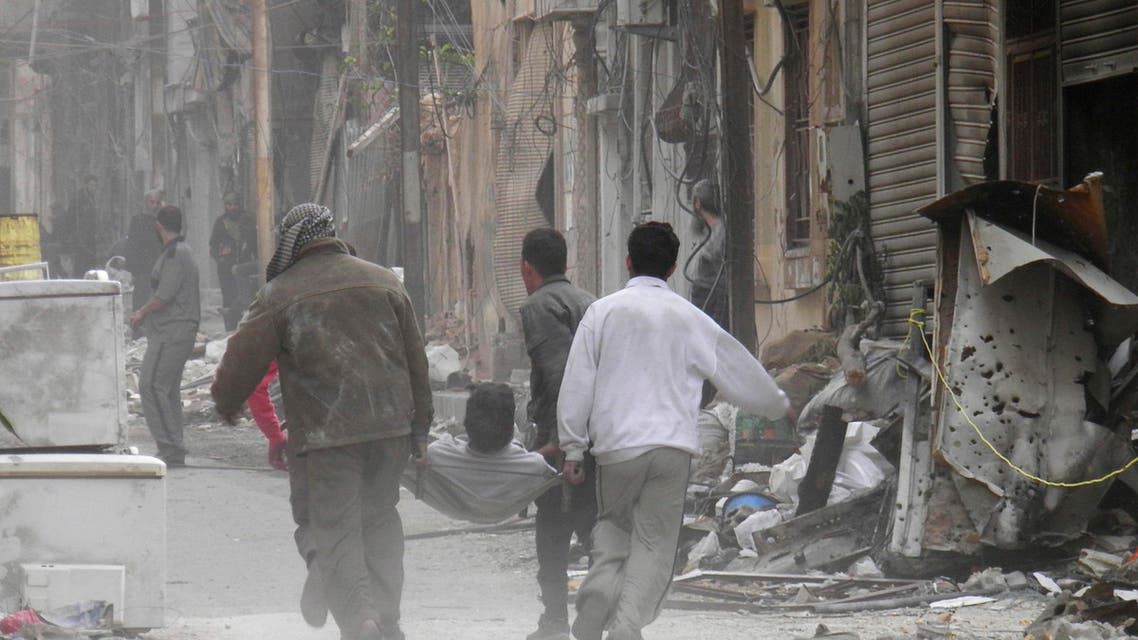 People carry a man on a stretcher injured due to shelling in the besieged area of Homs on November 25. (Reuters)