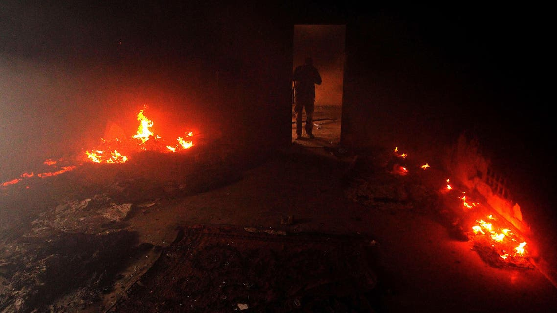 A Libyan man stands in a building used by Ansar al-Sharia militia after it was torched by residents on November 25, 2013 in Benghazi.