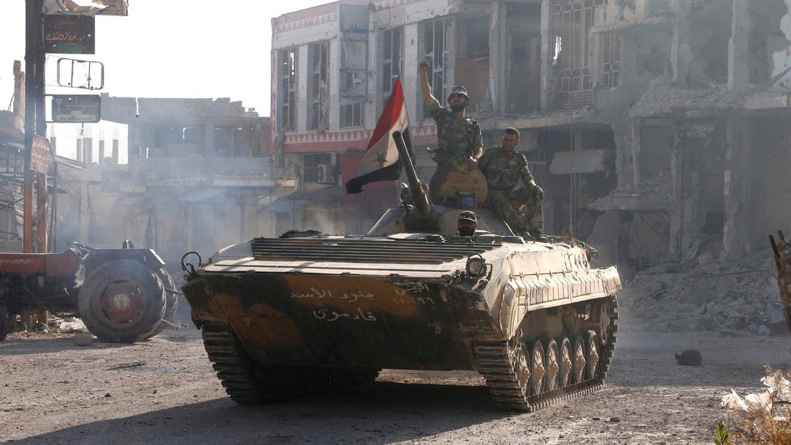 Soldiers loyal to the Syrian regime gesture while on their military tanks in Qusair. Syrian troops stormed Deir Attiyeh and has killed scores of civilians, opposition activists said. (File photo: Reuters)