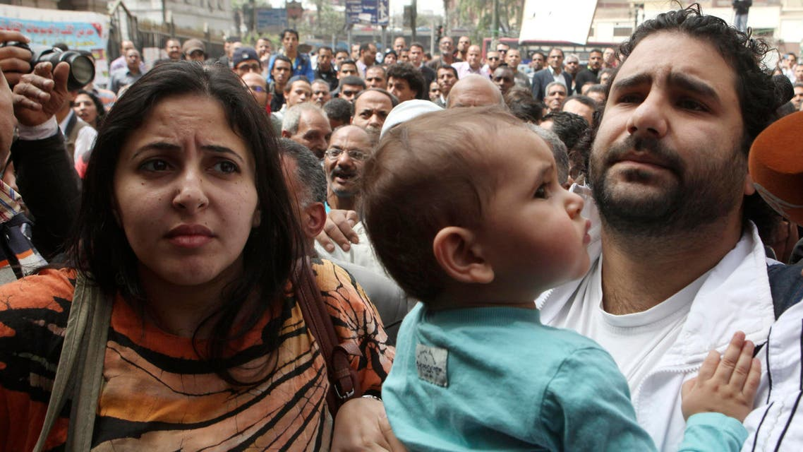 A file photo shows Alaa Abdel Fattah (R) arrives with his wife and child to the public prosecutor's office in Cairo, March 26, 2013. (Reuters)