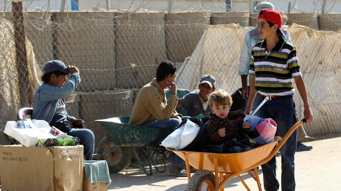 Syrian refugee children workers sit in wheelbarrows as they wait for customers at Al Zaatari refugee camp in the Jordanian city of Mafraq near the border with Syria November 20, 2013. reuters