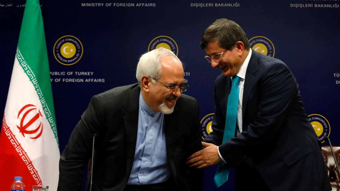 Turkish Foreign Minister Ahmet Davutoglu (R) helps Iranian Foreign Minister Mohammad Javad Zarif to stand during a news conference in Ankara Nov. 1, 2013. (Reuters)