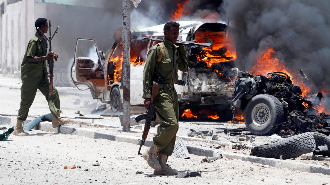Policemen walk past the scene of an explosion near the presidential palace in Somalia's capital Mogadishu, March 18, 2013. (Reuters)