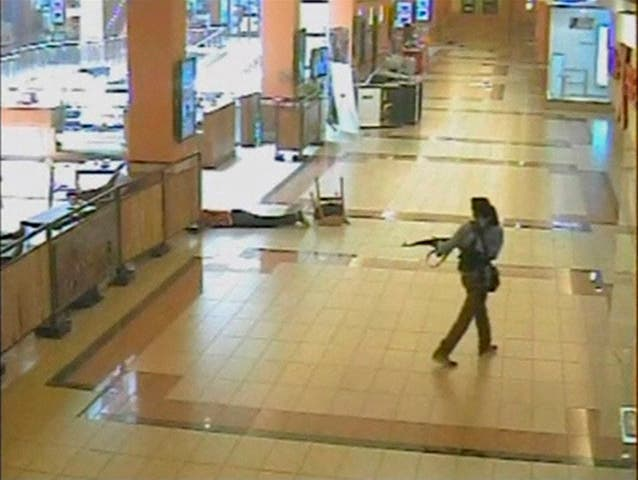 1.tA gunman points his rifle near an injured man (top, L) as he walks around during an attack, inside the Westgate shopping mall in this still frame taken from video footage by security cameras inside the mall in Nairobi and released to Reuters on October 17, 2013. Reuters