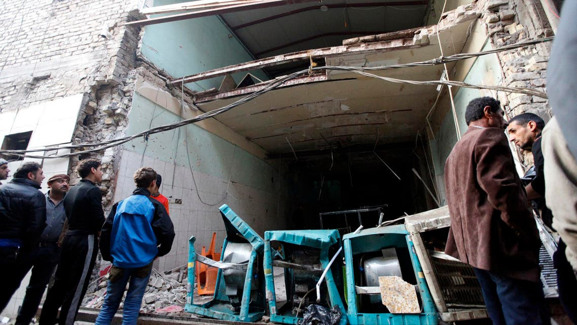 Residents look at the site of bomb attacks at a cafe in Baghdad's Sadriya district Reuters