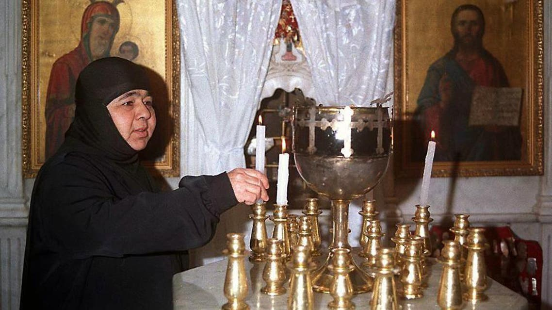 A Syrian nun lights candles inside the historical church of Mar Takla in the Christian village of Maalula, north of Damascus, on Dec. 24, 1998.  (Reuters)