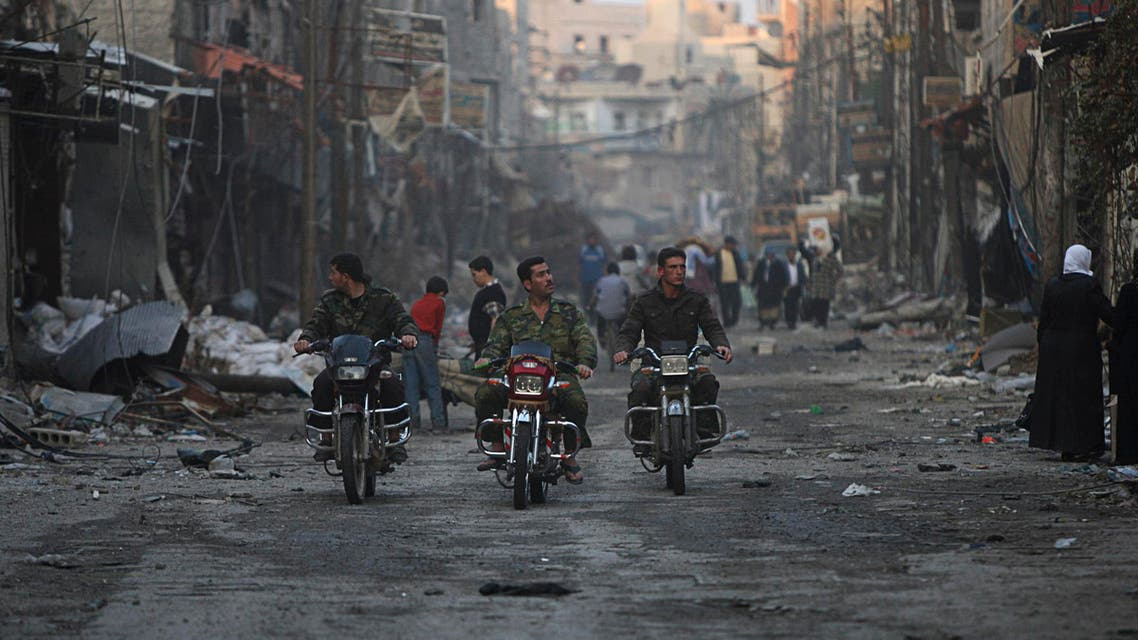 Security personnel loyal to Syria's President Bashar al-Assad ride motorcycles along a deserted street in Hujaira town, south of Damascus Nov. 21, 2013. (Reuters)