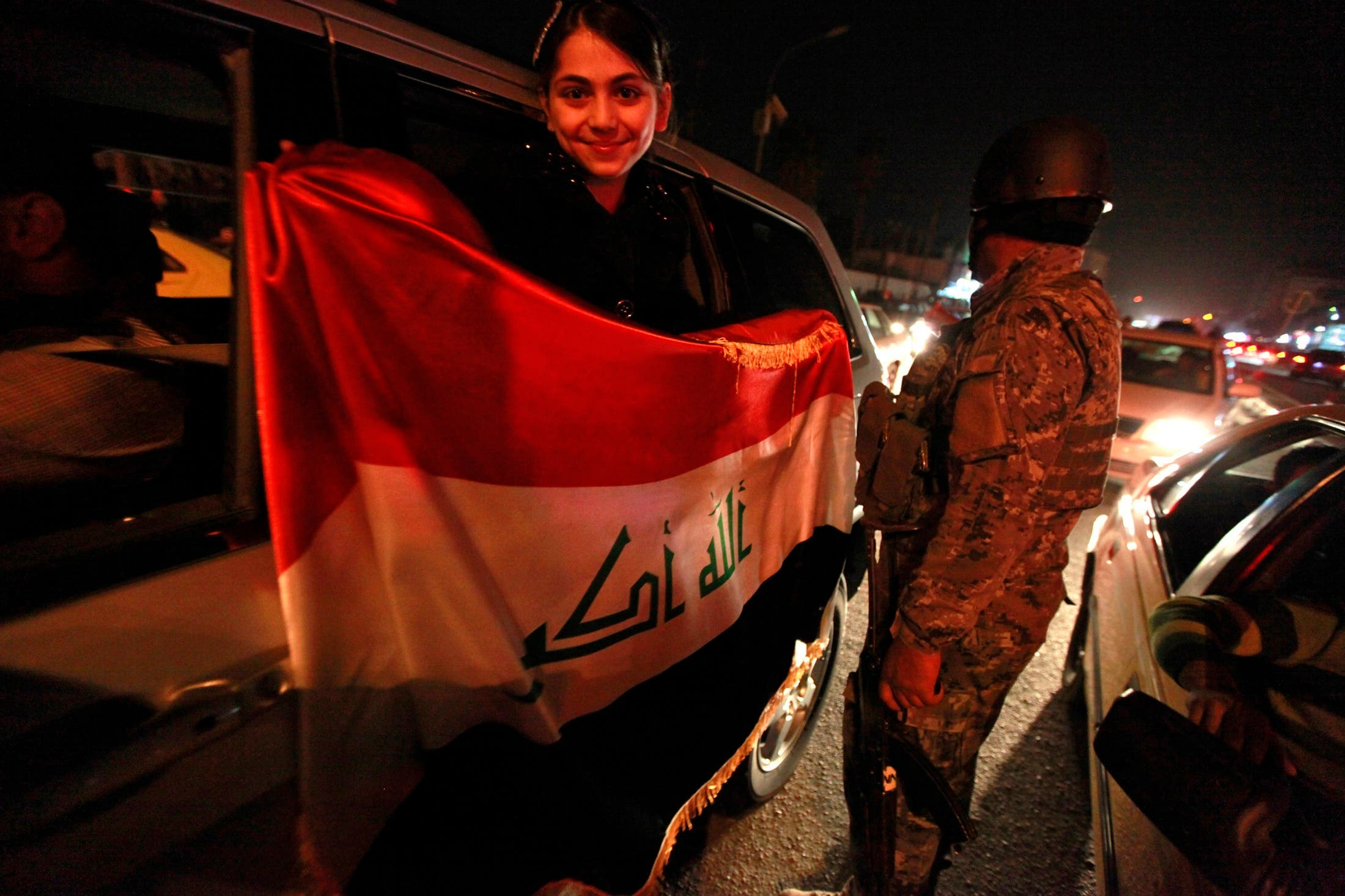 A girl holds the Iraqi national flag as she celebrates the victory of the Iraqi national soccer team over Singapore during their 2014 FIFA World Cup qualifier.  (Reuters)