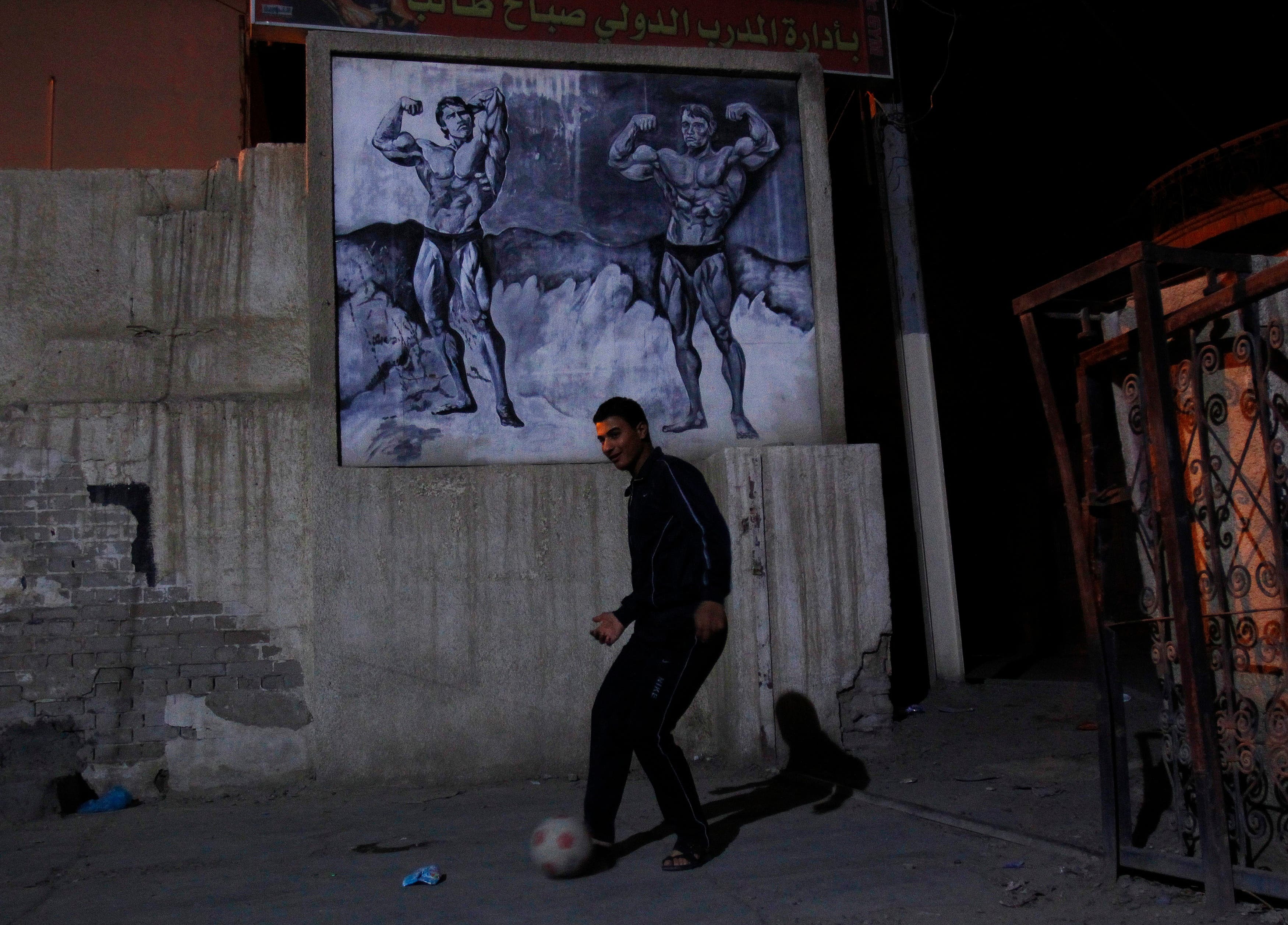 A boy plays soccer in the parking lot of a weightlifting gym in Baghdad, December 1, 2011. (Reuters)