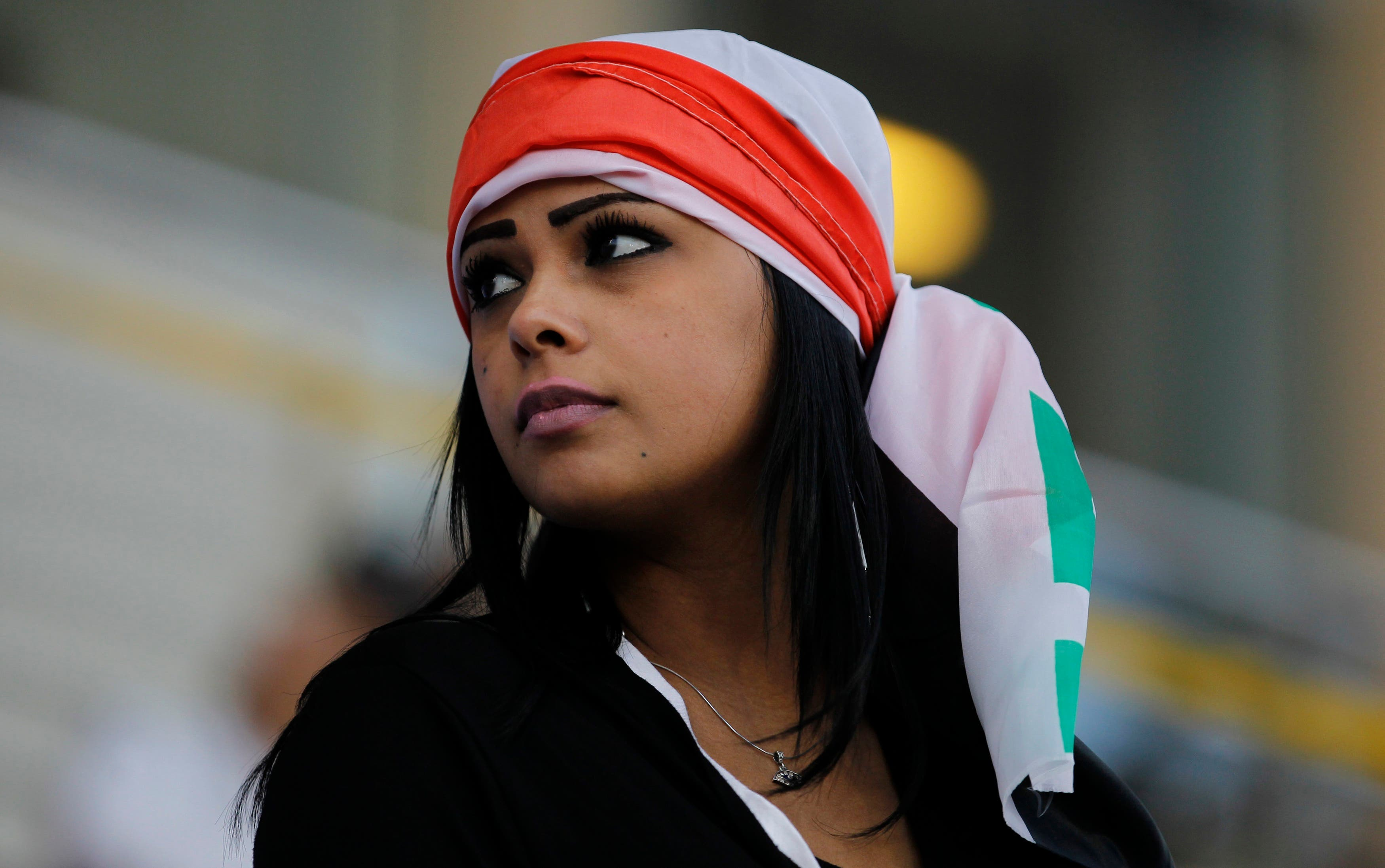 A fan wearing an Iraqi flag on her head arrives to watch their Gulf Cup Tournament soccer match against Yemen at Khalifa Sports City in Isa Town. (Reuters)