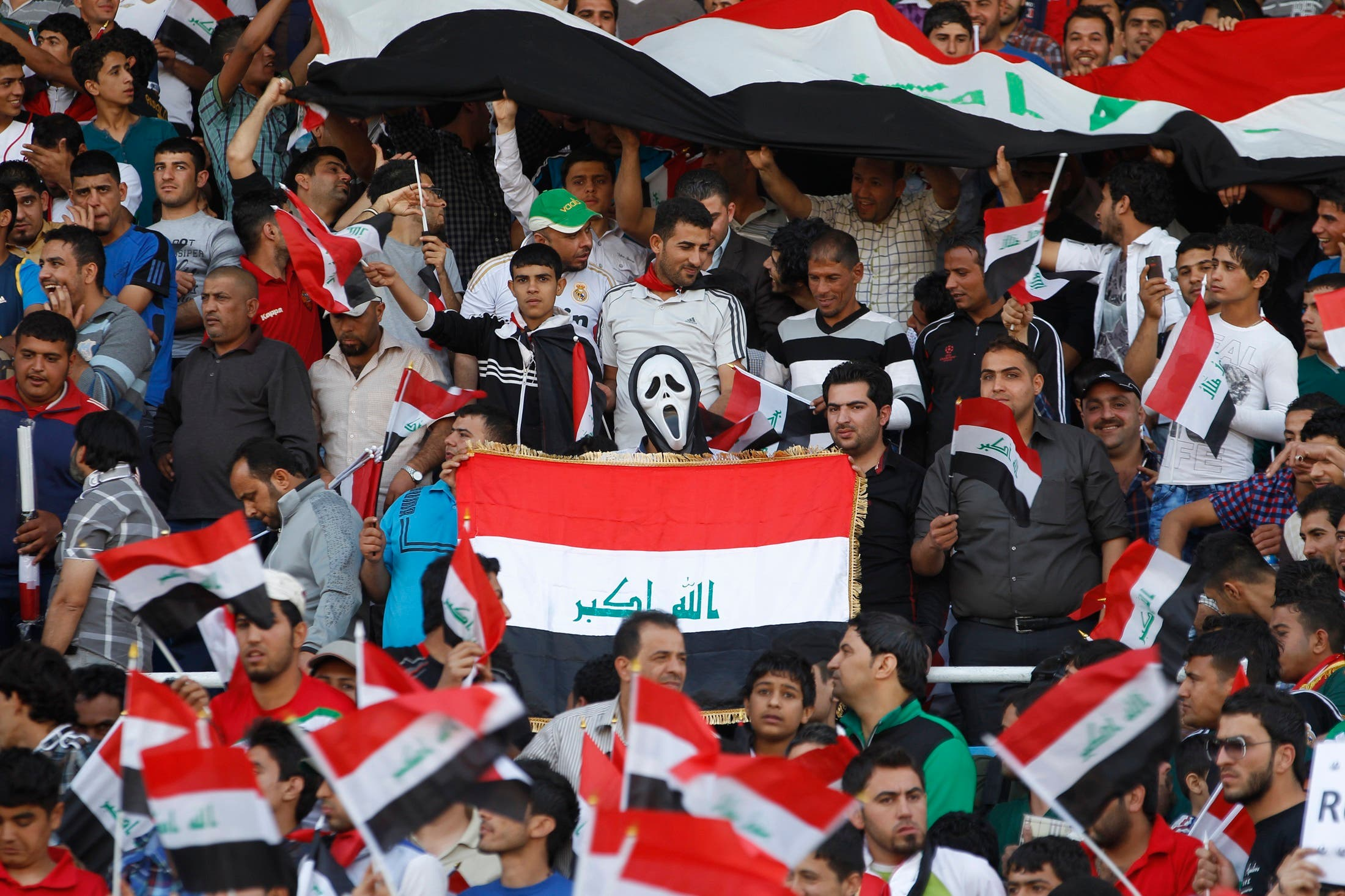 A fan wearing a Ghostface mask from Scream holds an Iraqi flag during Iraq's international friendly soccer match against Syria.(Reuters)