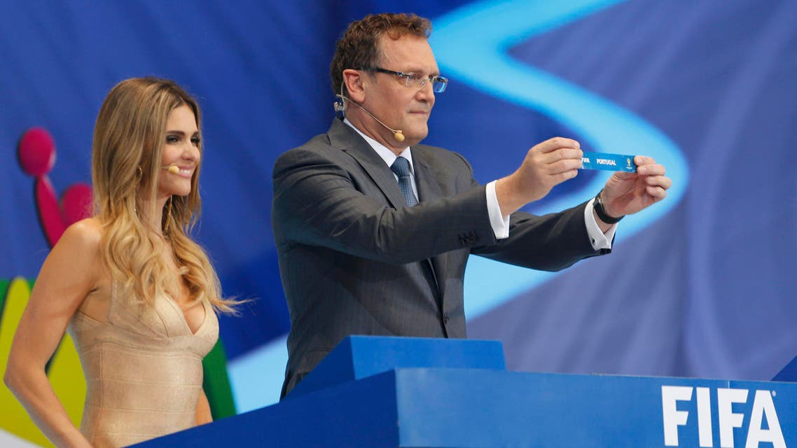 """FIFA Secretary General Jerome Valcke holds up the slip showing """"Portugal"""" next to presenter Fernanda Lima during the draw for the 2014 World Cup at the Costa do Sauipe resort in Sao Joao da Mata, Bahia state, December 6, 2013."""