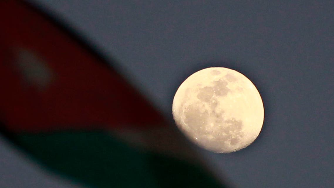 "A Jordanian National flag is pictured next to the moon during an anti-government rally organized by protesters known as ""Youth of March 24 Movement"" to demand for more freedom and access to corruption cases in Amman March 24, 2013."