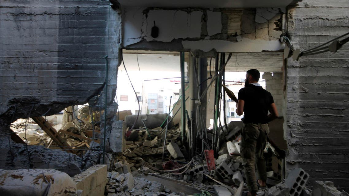 A member of the Kefah Brigade, which is part of the Asood Allah Brigade operating under the Free Syrian Army, holds his weapon in a damaged building at one of the battlefronts in Jobar, a suburb of Damascus September 20, 2013. (Reuters)