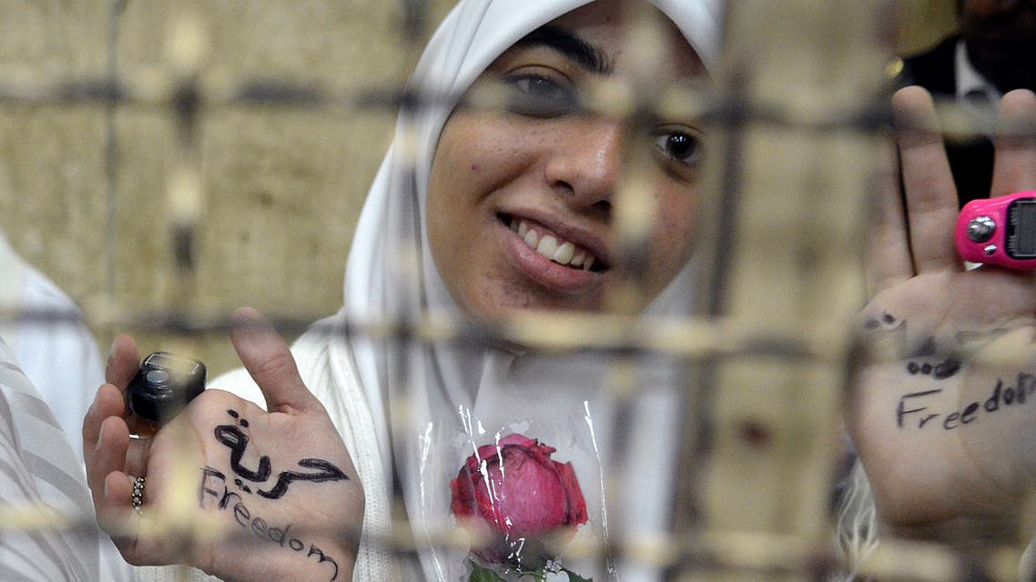 Egyptian women members of the Muslim Brotherhood hold roses as they stand in the defendants' cage dressed in prison issue white during their trial in at the court in Alexandria on Dec.7, 2013. (AFP)