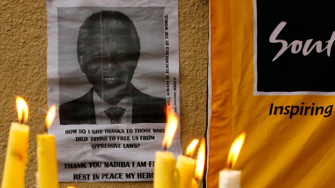 Candles burn in front of a poster of Nelson Mandela as mourners pay homage outside the Houghton home of the late former South African President in Johannesburg December 8, 2013.  reuters