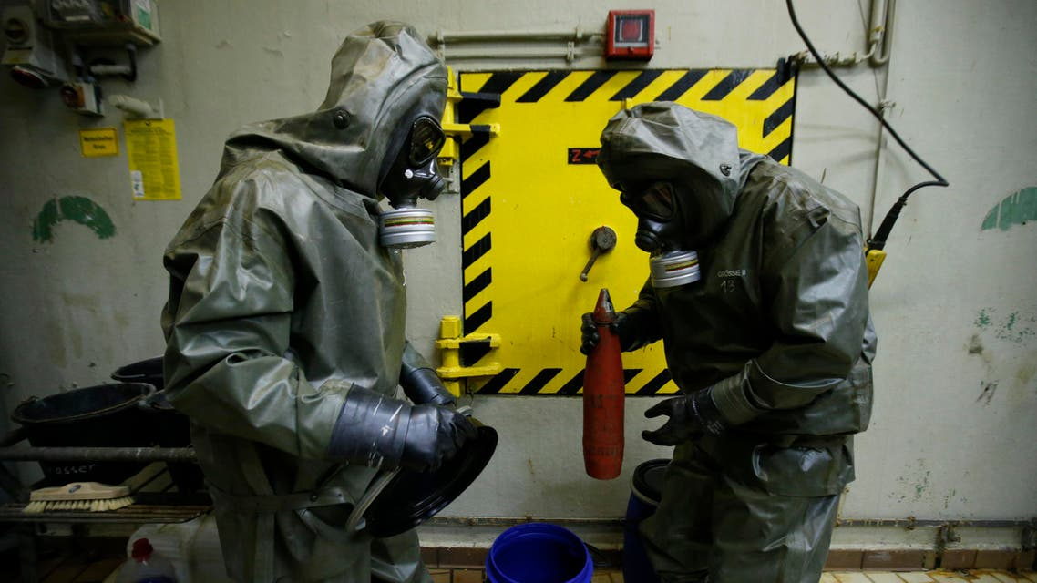 Workers dressed in protective clothing prepare a dummy chemical grenade for destruction at the Society for the Disposal of Chemical Weapons and Ordnance. (File photo: Reuters)