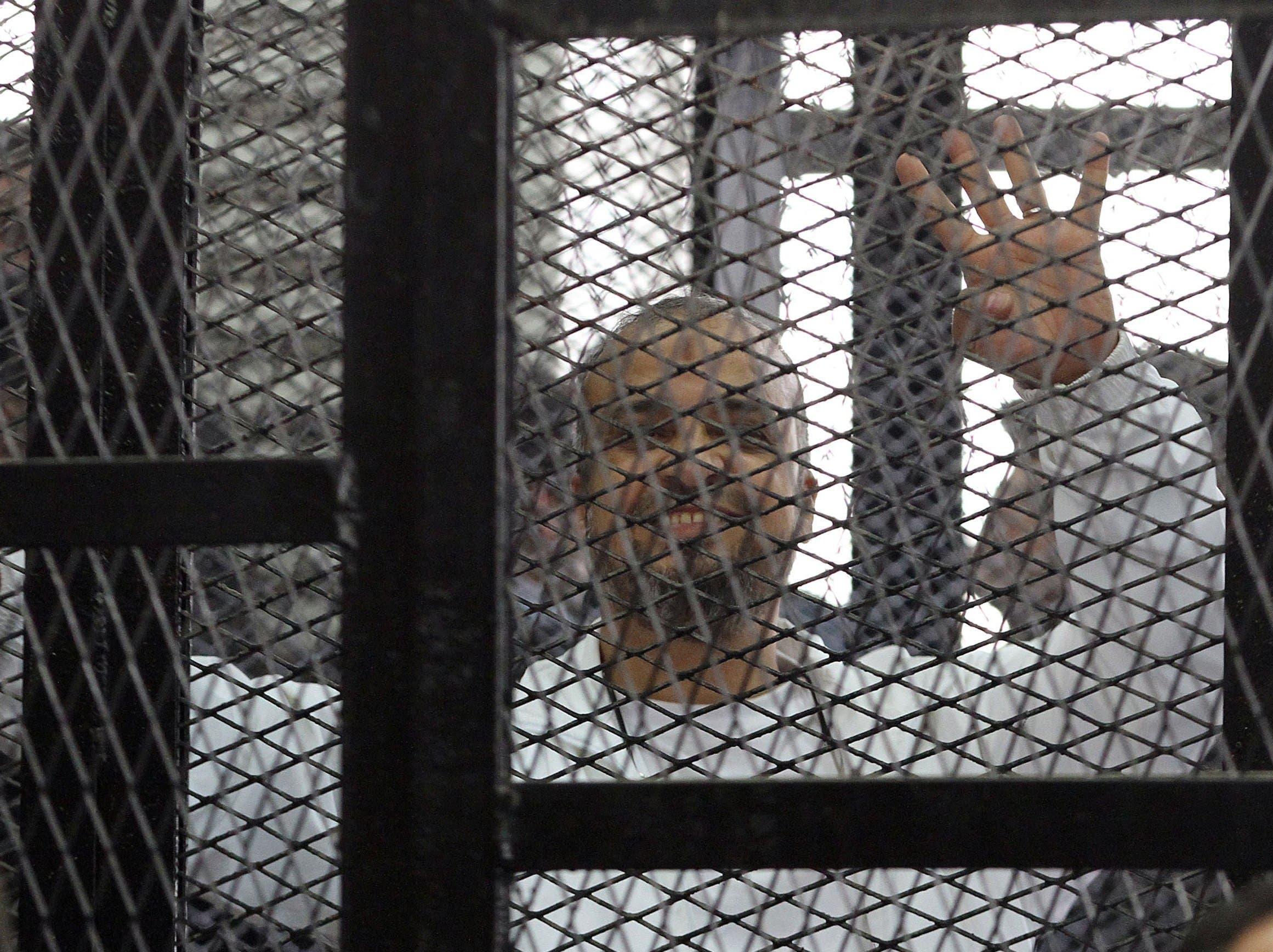 """محمد البلتاجي يشير بعلامة رابعة من داخل قفص الاتهام أثناء محاكمته """"أرشيفية"""""""