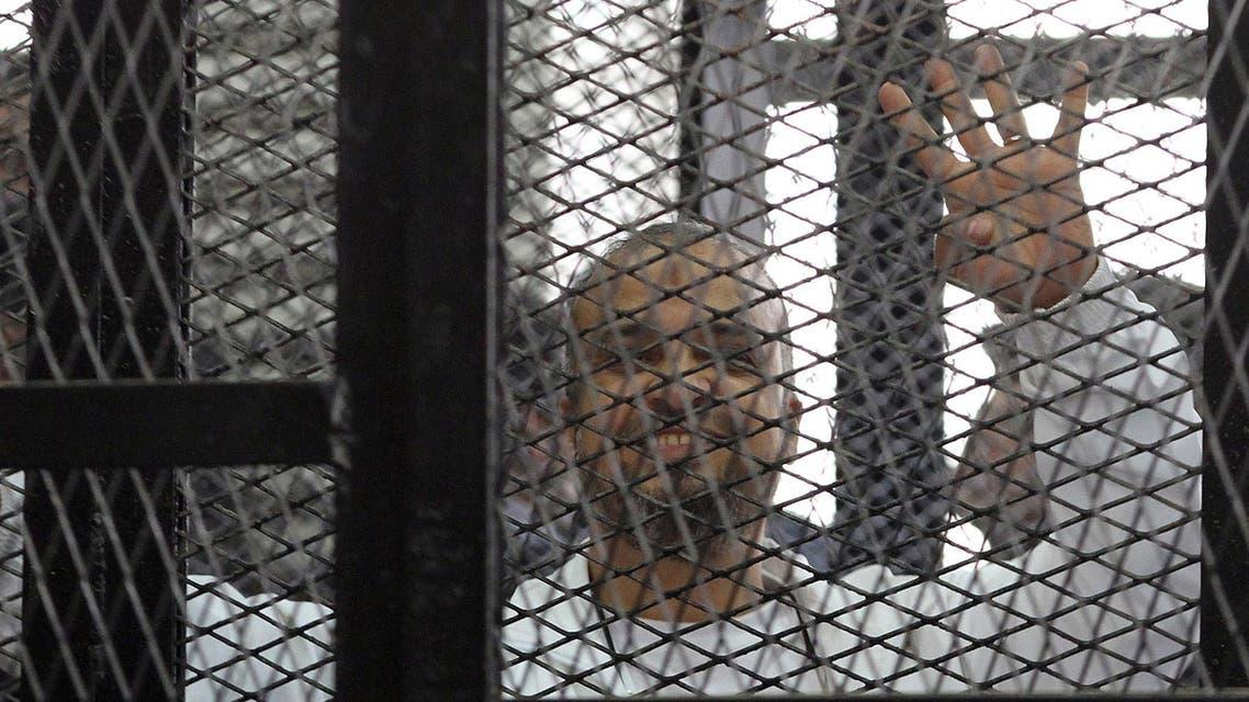 محمد البلتاجي يشير بعلامة رابعة من داخل قفص الاتهام