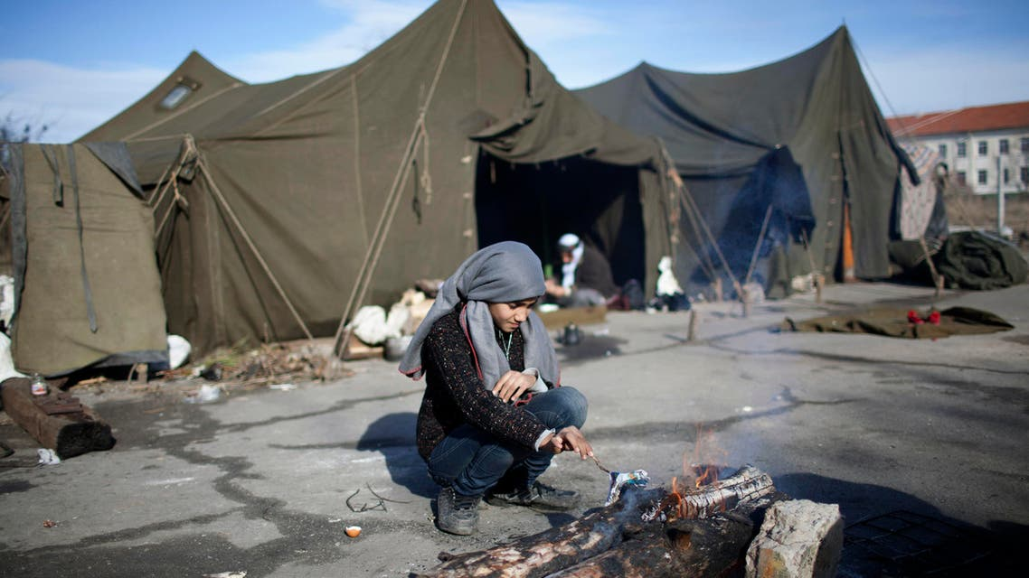 A Syrian girl prepares a fire in front of tents at a refugee camp in Harmanli, 280 km (173 miles) east of Sofia, December 9, 2013.