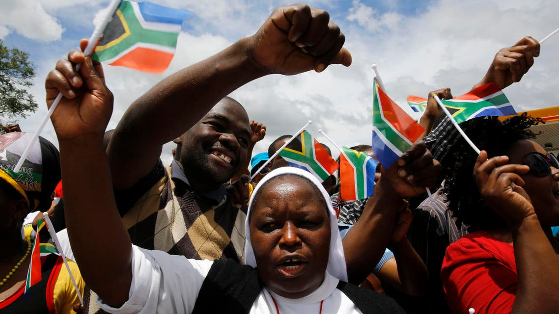 A Catholic nun and other mourners march before the arrival of the body of former South African President Nelson Mandela in the center of Mthatha, Dec. 14, 2013. (Reuters)