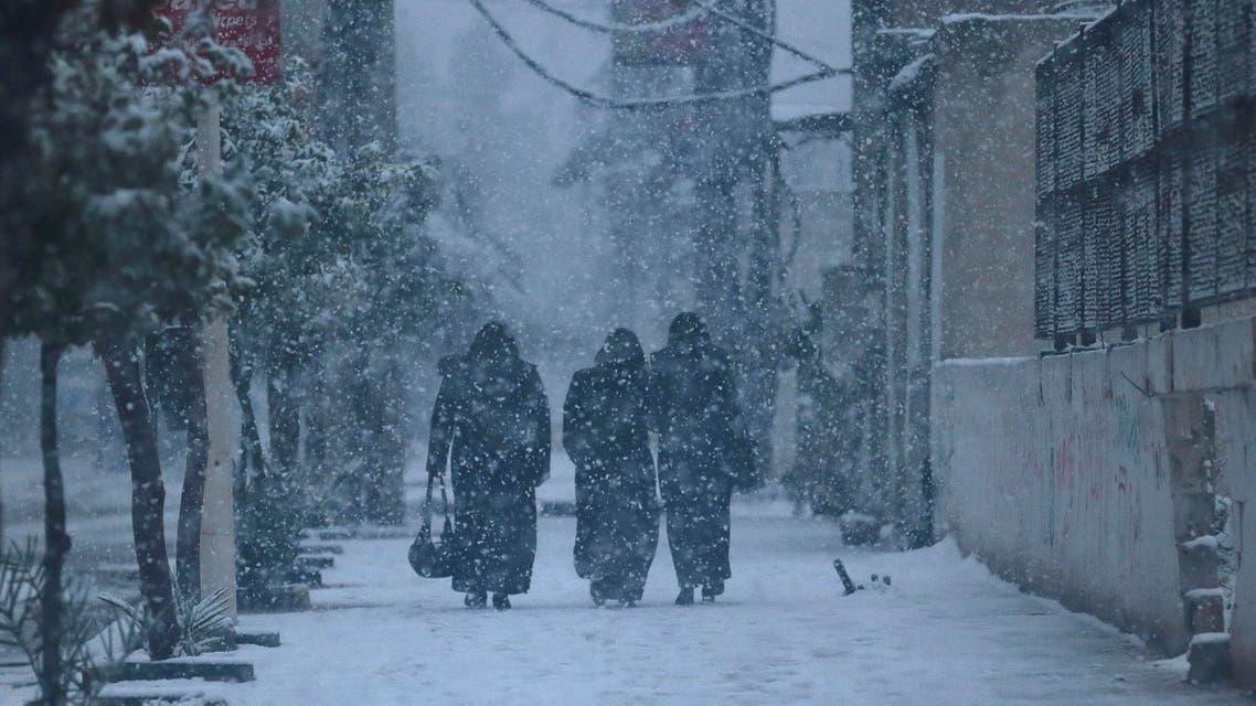 People walk along a street during snow fall in the Duma neighbourhood of Damascus, December 13, 2013.