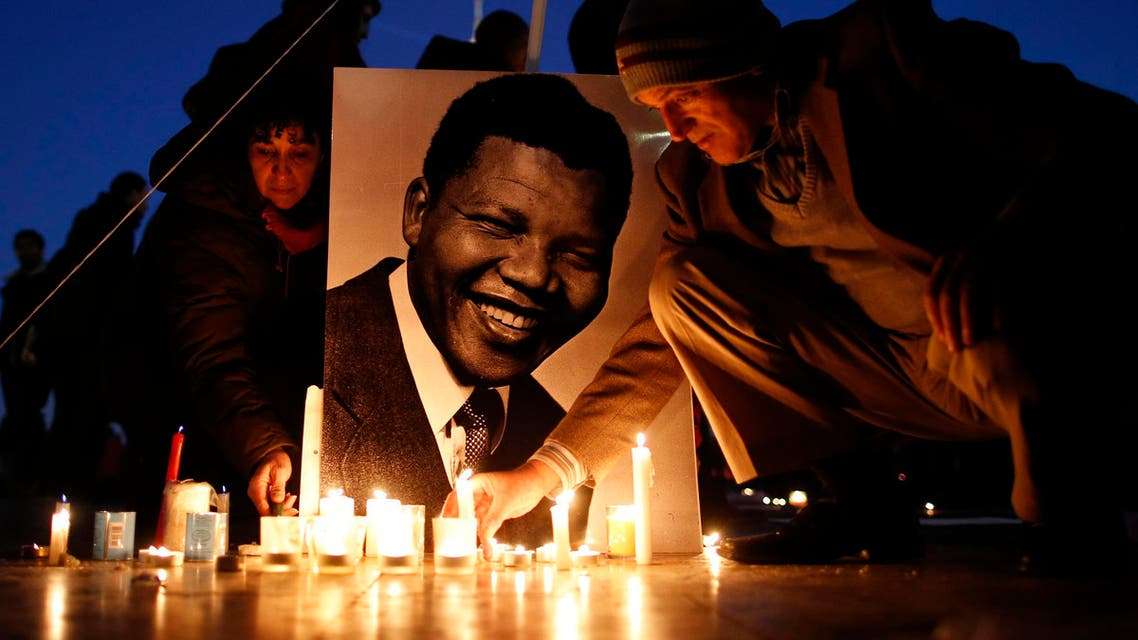 People place candles near a photo as they pay tribute to former South African President Nelson Mandela at the Trocadero square, in front of the Eiffel Tower in Paris December 15, 2013. (Reuters)