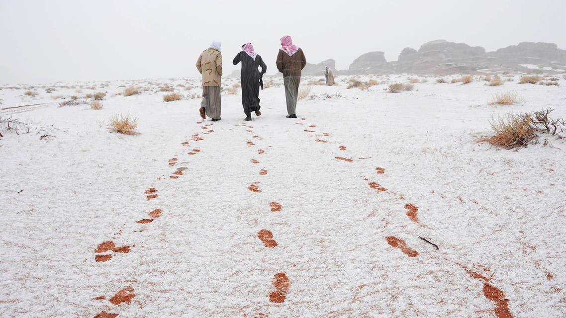 Saudi men walk as their footprints are seen after a snowstorm in Alkan village, west of Saudi Arabia December 13, 2013.