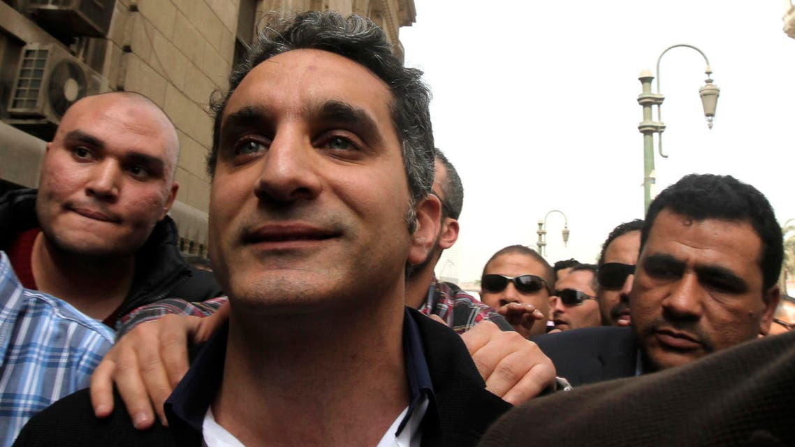 Bassem Youssef gestures to journalists and activists as he arrives to appear at the prosecutor's office in Cairo in March 31, 2013. (File photo: Reuters)
