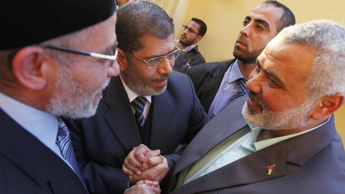 Senior Hamas leader Ismail Haniyeh (R) shakes hands with Mohamed Mursi (C), Egypt's ousted president, and Egyptian Muslim brotherhood leader Mohammed Badie before an earlier meeting in Cairo. (File photo: Reuters)