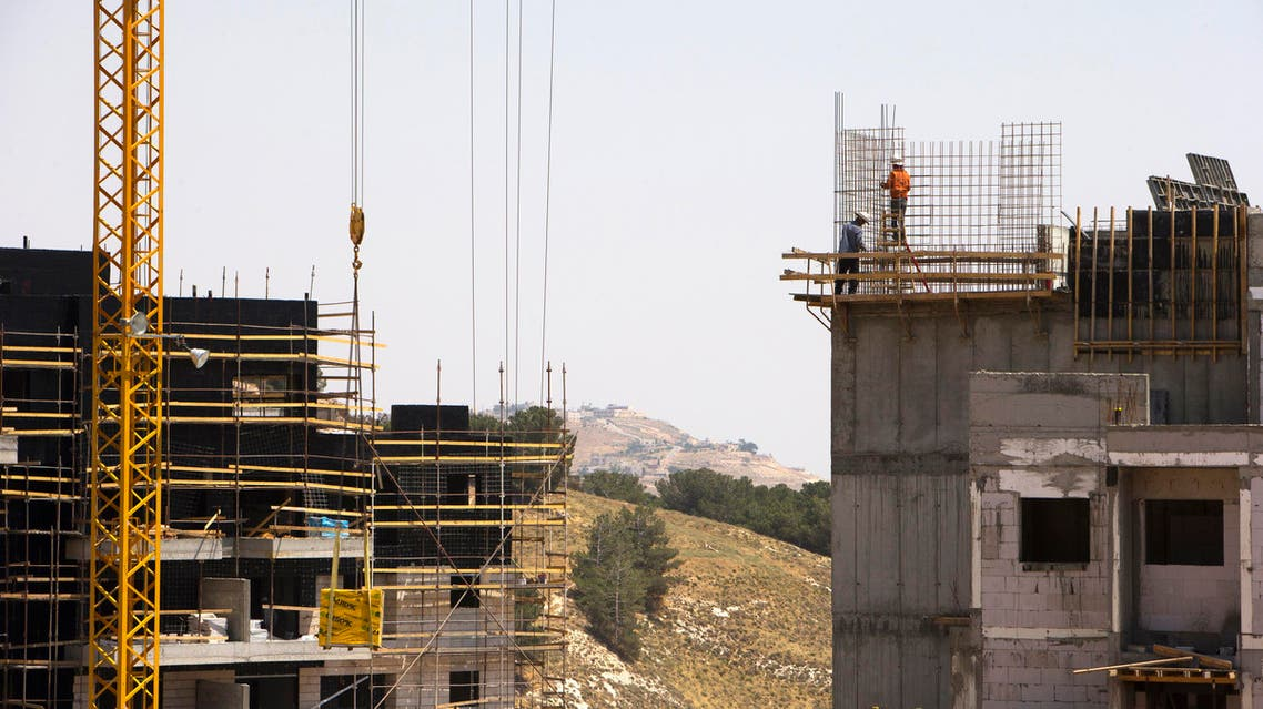 Laborers work on a construction site in a Jewish settlement near Jerusalem known to Israelis as Har Homa and to Palestinians as Jabal Abu Ghneim, pictured in May 2013. (File photo: Reuters)