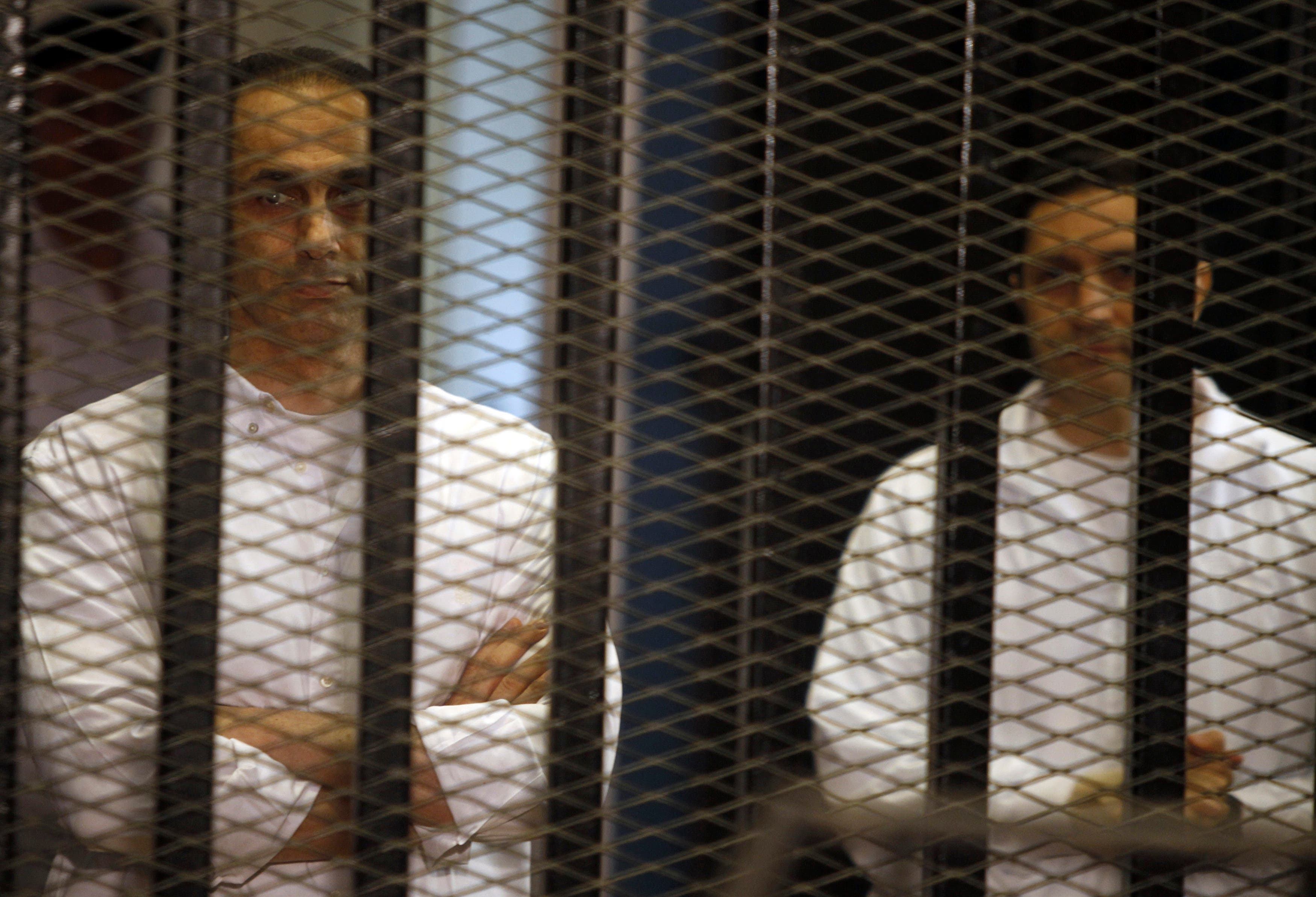 Gamal (L) and Alaa Mubarak, sons of former Egyptian President Hosni Mubarak, stand behind bars during a court trial on June 8, 2013. (File photo: Reuters)