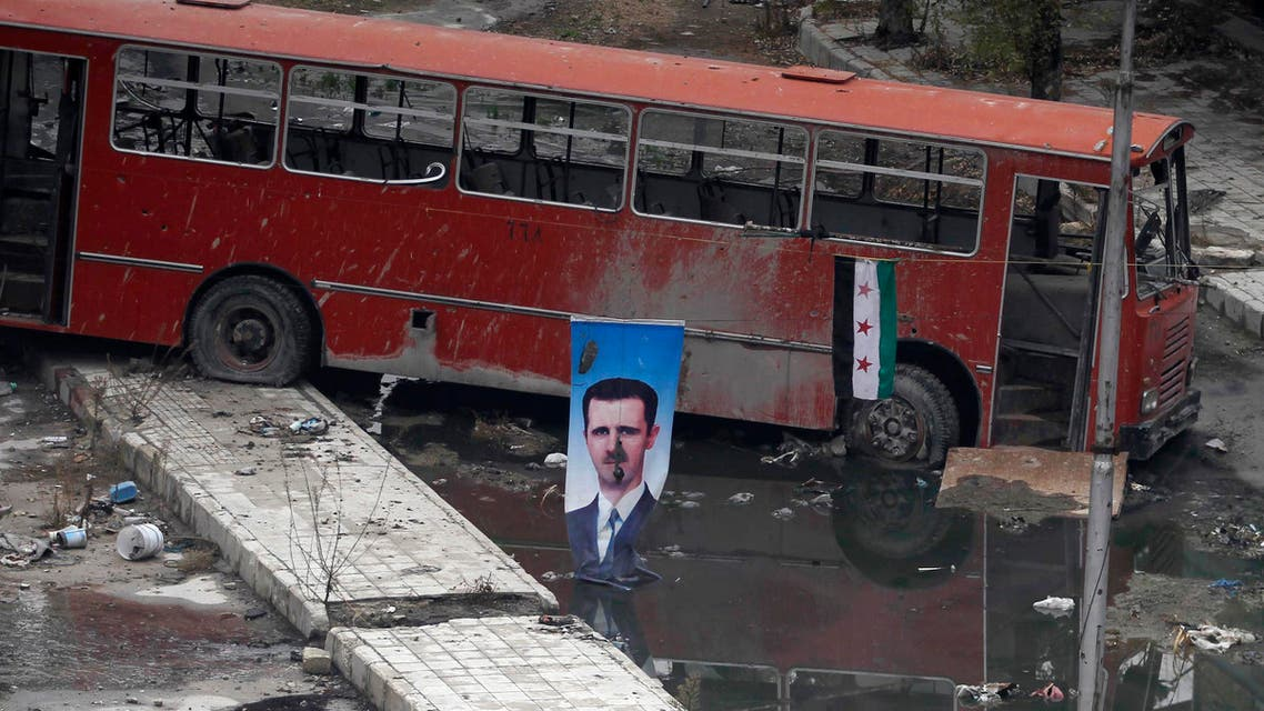 A picture of Syrian President Bashar al-Assad is seen near a Syrian opposition flag in Aleppo's Bustan al-Basha district on Dec. 3. (File photo: Reuters)