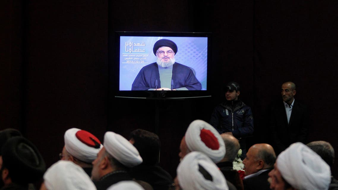 Shi'ite and Sunni Muslim clerics listen to Lebanon's Hezbollah leader Sayyed Hassan Nasrallah addressing his supporters via a screen during a ceremony to mark the death of Hezbollah commander Hasan al-Laqqis in Beirut's southern suburbs December 20, 2013. reuters