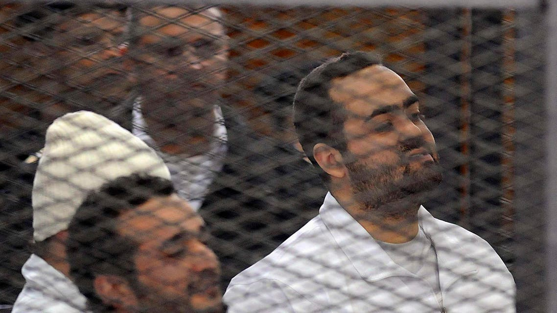 Political activists Ahmed Maher (in white hat), Ahmed Douma (L) and Mohamed Adel (R) of the 6 April movement look on from behind bars in Abdeen court in Cairo, Dec. 22, 2013. (Reuters)