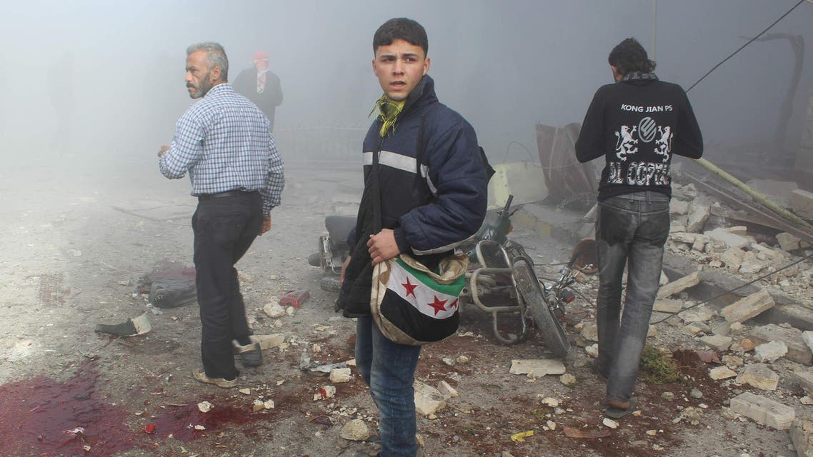 A youth carrying a bag depicting a Syrian opposition flag inspects with others a site hit by what activists say are barrel bombs dropped by government forces at Maaret al-Naaman town in Idlib, Dec. 23, 2013. (Reuters)