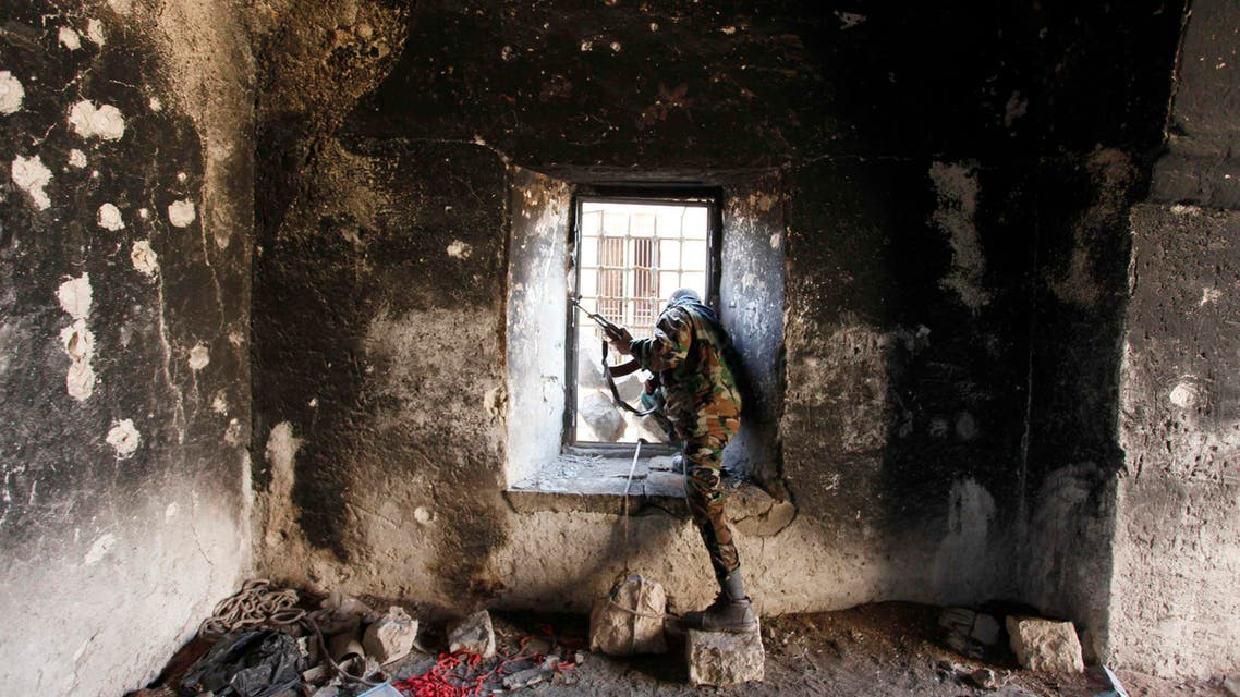 A Free Syrian Army fighter looks through a window of a damaged house in Old Aleppo, December 15, 2013.